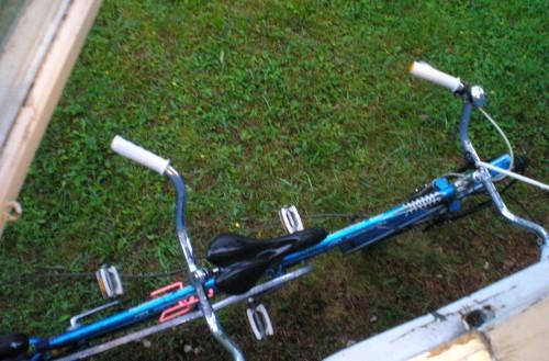 En blöt tandemcykel får sova nedanför vandrarhemmets fönster