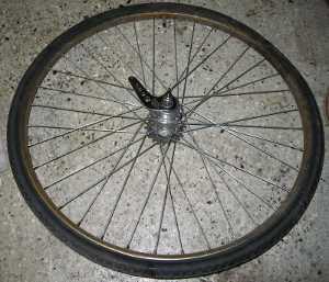 Fotbromsat bakhjul avmonterat, bromsarmen synlig vid navet.