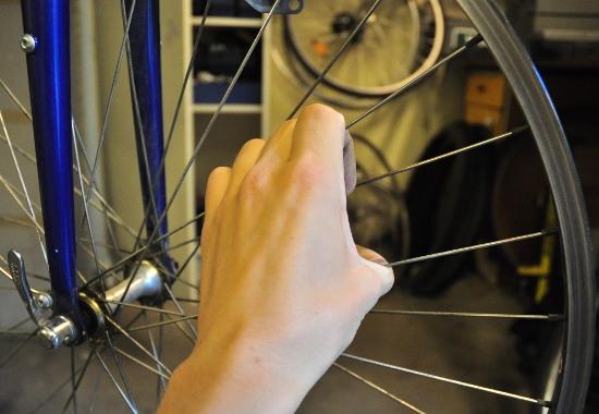 Att klämma hjulets alla ekrar mot varandra i par är ett bra sätt att upptäcka om det finns stora skillnader i ekerspänningen.